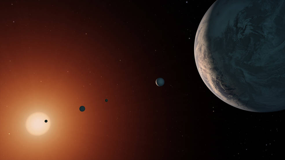 This illustration shows what the TRAPPIST-1 system might look like from a vantage point near planet TRAPPIST-1f (at right)