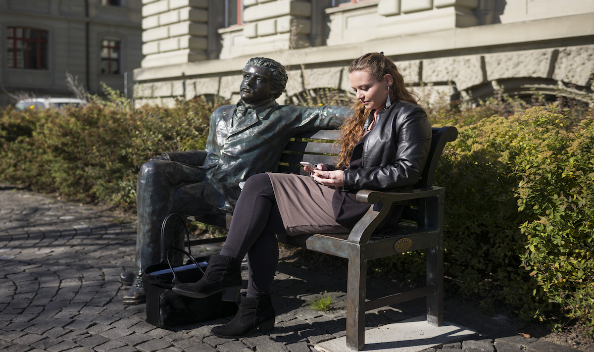 Bronze bench with life-sized Einstein statue and a real young woman with long hair sitting next to it